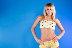 Portrait of a cute blonde girl. Beautiful blonde in yellow on a blue background Royalty Free Stock Photos