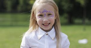 Portrait of a cute blonde girl with aqua makeup. Child with funny face painting stock video