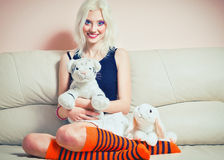 Cute blonde girl with rabbit and tiger toys Stock Photography