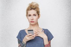 Portrait of cute blonde girl with tattoos hanging cell phone and become confused because her boyfriend has bad news. Isolated over white wall. Emotional Stock Images