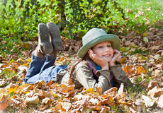 Portrait of cute blue-eyed girl with hat relaxing in autumn park Royalty Free Stock Images