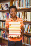 Portrait of cute boy carrying books in library Stock Photography