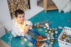 Portrait of A Cute boy with a christmas lights. Sits on a floor Royalty Free Stock Photo