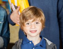 Portrait Of Cute Boy At Cinema. Portrait of cute boy with parents standing in background at cinema Royalty Free Stock Images
