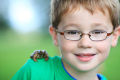 Portrait of a cute boy with glasses. And a frog on the shoulder focus on boy Royalty Free Stock Images
