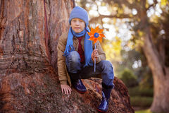Portrait of cute boy holding pinwheel while crouching on tree trunk Stock Photo