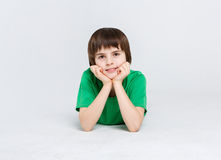 Portrait of a cute boy lying on the floor on white background. Portrait of a dreamy boy lying on the floor at white studio background. Kid in casual bright Stock Photography