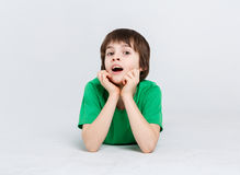 Portrait of a cute boy lying on the floor on white background. Portrait of surprised boy lying on the floor at white studio background. Kid in casual bright Royalty Free Stock Photography