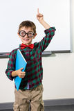 Portrait of cute boy with notebook raising hand in classroom. Portrait of cute boy with notebook raising hand against whiteboard in classroom Royalty Free Stock Photo