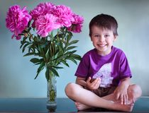 Portrait of a cute boy with peonies Royalty Free Stock Photos