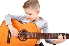Portrait of a cute boy playing acoustic guitar. On white background stock image