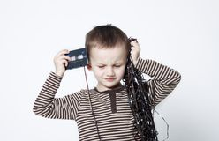 Portrait of cute boy playing with old tape. Portrait of cute little boy with playing with old tapes on white background Royalty Free Stock Photo