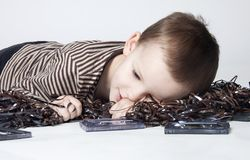 Portrait of cute boy playing with old tape. Portrait of cute little boy with playing with old tapes on white background Royalty Free Stock Images