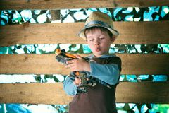 Portrait of a cute boy playing with a pistol Stock Image