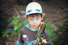 Portrait of a cute boy playing with a pistol Royalty Free Stock Photo