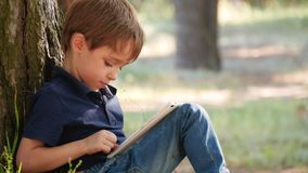Portrait of a cute boy of preschool age. The child sits at a tree in the Park and spends time playing in the tablet. stock video footage
