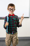 Portrait of cute boy raising hand in classroom. Portrait of cute boy raising hand against whiteboard in classroom Royalty Free Stock Photos