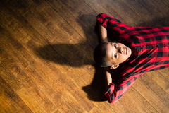 Portrait of cute boy relaxing on wooden floor. At home Royalty Free Stock Images