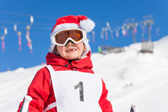 Portrait of cute boy in Santa`s hat at snowy hill Stock Image