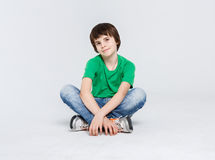 Portrait of a cute boy sitting on the floor on white background. Portrait of a dreamy boy sitting on the floor at white studio background. Kid in casual bright Royalty Free Stock Photography