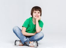 Portrait of a cute boy sitting on the floor on white background. Portrait of happy smiling boy sitting on the floor at white studio background. Kid in casual Stock Images