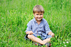 Portrait of cute boy sitting on green grass Royalty Free Stock Image