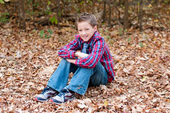 Portrait of cute boy sitting in leaves with legs crossed. Stock Image