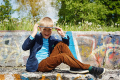 Portrait Cute boy sitting in park and using tablet pc. Educating Stock Images