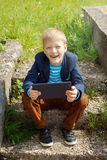Portrait Cute boy sitting in park and using tablet pc Royalty Free Stock Images