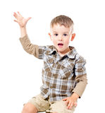 Portrait of a cute boy sitting with raised hand Royalty Free Stock Photography