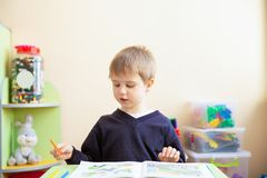 Portrait of cute boy with sketch pen and book at desk in classroom royalty free stock image
