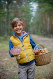 Cute boy with wild mushroom found in the forest Stock Photos
