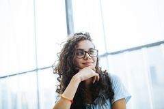 Cute brazilian girl with curly hair listening to a conversation and has an idea royalty free stock image