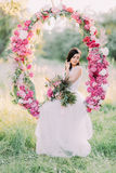 The portrait of the cute bride holding the bouquet of flowers and sitting in the wedding peonies arch in the sunny field Royalty Free Stock Photography