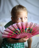 Portrait - cute on bright background little girl with a fan Stock Photography