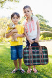 Portrait of cute brother and sister posing with old luggage and teddy bear Royalty Free Stock Photo