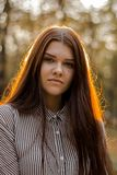 Portrait of a cute brown-haired girl whose sunset sunlight shimmers in her hair. A young lady with a confident smile looks straight royalty free stock photography