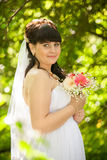 Portrait of cute brunette bride at summer park Royalty Free Stock Image