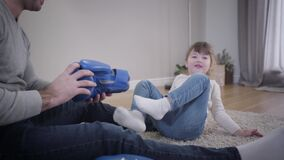 Portrait of cute brunette Caucasian girl sitting with adult man and playing with boxing gloves. Young father spending stock footage