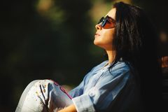 Portrait of cute brunette girl wears sunglasses and dreaming looking at the sun. Beautiful woman with round glasses from sunlight Stock Image
