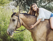 Portrait of the cute brunette woman riding a horse Stock Images