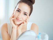 Portrait of a cute brunette woman touching her cheeks Royalty Free Stock Image