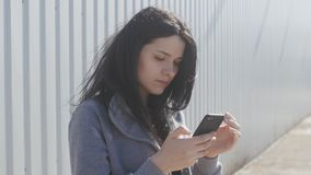 Portrait of young woman using smartphone outdoor on the street. The wind easily waves her hair. Portrait of cute brunette woman using smartphone outdoor on the stock video