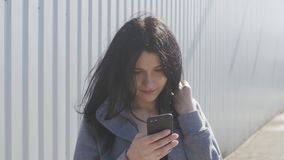 Portrait of cute brunette woman using smartphone outdoor on the street. The wind easily waves her hair. Portrait of cute brunette woman using smartphone outdoor stock footage