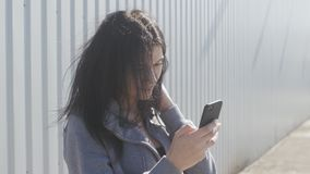 Portrait of cute brunette woman using smartphone outdoor on the street. The wind easily waves her hair. Portrait of cute brunette woman using smartphone outdoor stock video