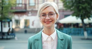 Portrait of cute businesswoman in glasses standing alone in the street smiling stock footage
