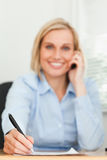 Portrait of a cute businesswoman on mobile noting Stock Photo