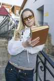 Portrait of Cute Caucasian Blond Female Reading Book Posing Outdoors in City. Standing on Stairs.Vertical Image Composition Royalty Free Stock Images