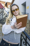 Portrait of Cute Caucasian Blond Female Reading Book Posing Outdoors in City. Standing on Stairs. Vertical Image Orientation Royalty Free Stock Image