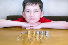 Boy with coins. Portrait of a cute caucasian boy looking at camera. A pile of coins is on the table surface Stock Photography